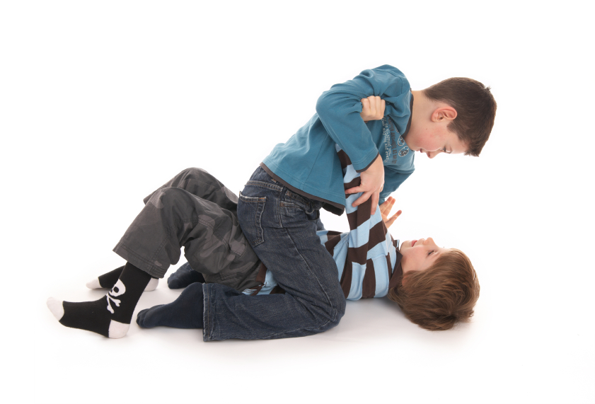 two boys fighting on white floor